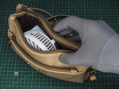 Попытка засунуть ручной складной вентилятор в женскуюю сумочку